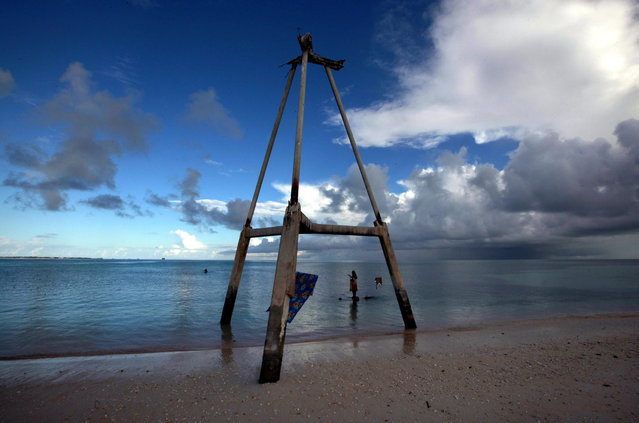 Binata Pinata stands on top of a rock underneath an old tower as she waits for her husband Kaibakia to hand her the fish he is catching, on Bikeman islet, located off South Tarawa in the central Pacific island nation of Kiribati May 25, 2013. (Photo by David Gray/Reuters)