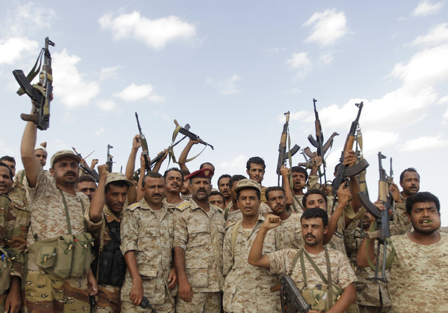 Military men wave their weapons at an army post at al-Mahfad, in the southern Yemeni province of Abyan May 23, 2014. (Photo by Khaled Abdullah/Reuters)