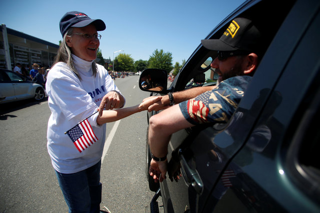 Joseph Rice (R), greets a supporter of the Josephine County Oath Keepers, which later disbanded and became the Liberty Watch of Josephine County, during a Memorial Day parade in Grants Pass, Oregon, U.S. May 28, 2016. (Photo by Jim Urquhart/Reuters)