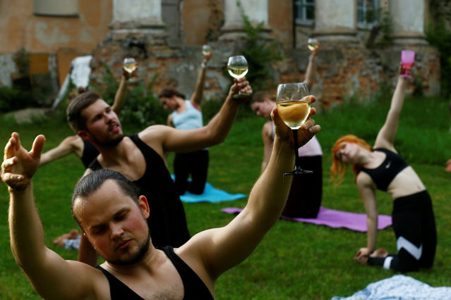 People hold glasses of wine as they perform wine yoga in Riga, Latvia on August 8, 2020. (Photo by Ints Kalnins/Reuters)