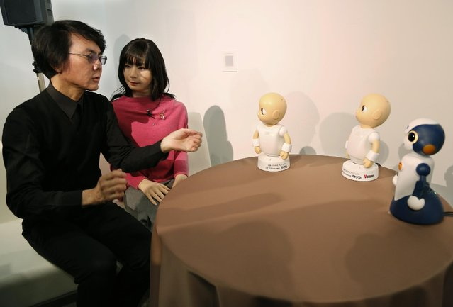 Japanese android expert Hiroshi Ishiguro, left, talks with new talking robot Sota, right, Android robot Otonaroid, second left, and another talking robots CommU, center and second right, during a press event at the National Museum of Emerging Science and Innovation Miraikan in Tokyo Tuesday, January 20, 2015. (Photo by Shizuo Kambayashi/AP Photo)