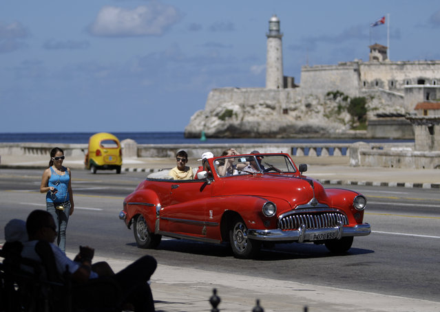 In this October 12, 2013 file photo, tourists ride in a classic American car on the Malecon in Havana, Cuba. (Photo by Franklin Reyes/AP Photo)