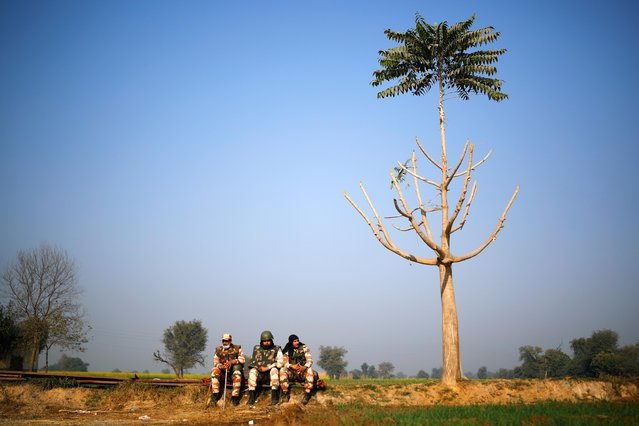 Policemen sit near the site of a protest against new farm laws, at a state border on a national highway in Shahjahanpur, in the desert state of Rajasthan, near New Delhi, India, December 26, 2020. (Photo by Adnan Abidi/Reuters)