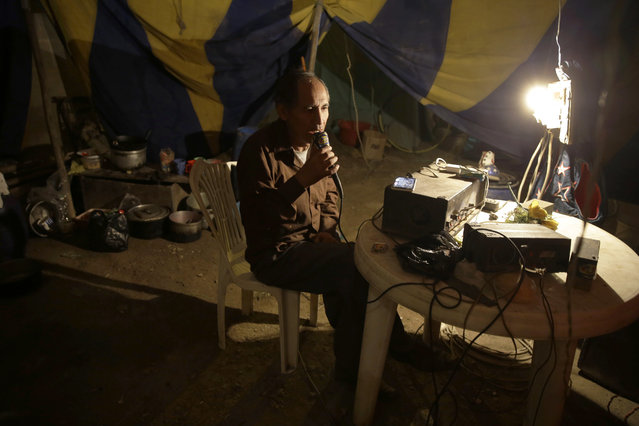 In this July 8, 2018 photo, circus owner and clown Jose Alvarez talks into a speaker system to announce the soon-to-start opening act, as he sits under the circus tent set up in the shantytown of Puente Piedra on the outskirts of Lima, Peru. One night, Alvarez tallied the ticket sales for the circus named after his father and sighed when he realized they'd earned less than $40. (Photo by Martin Mejia/AP Photo)