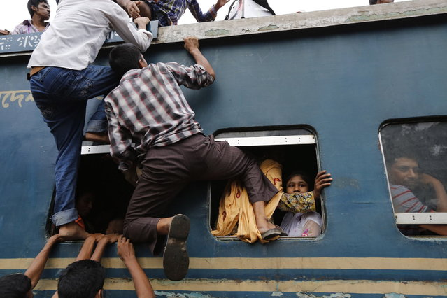 Passengers try to climb to the top of an overcrowded train at a railway station in Dhaka August 8, 2013. Millions of residents in Dhaka are travelling home from the capital city to celebrate the Muslim Eid al-Fitr holiday, which marks the end of the holy fasting month of Ramadan. (Photo by Andrew Biraj/Reuters)
