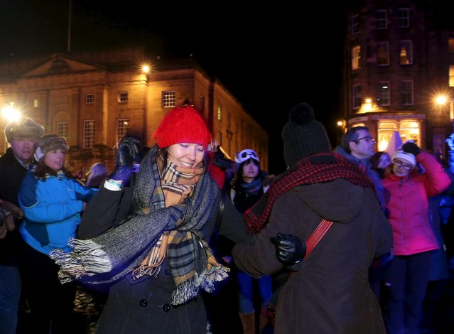 People dance in the streets during the Hogmanay celebrations in Edinburgh, Scotland, December 31, 2015. (Photo by Russell Cheyne/Reuters)