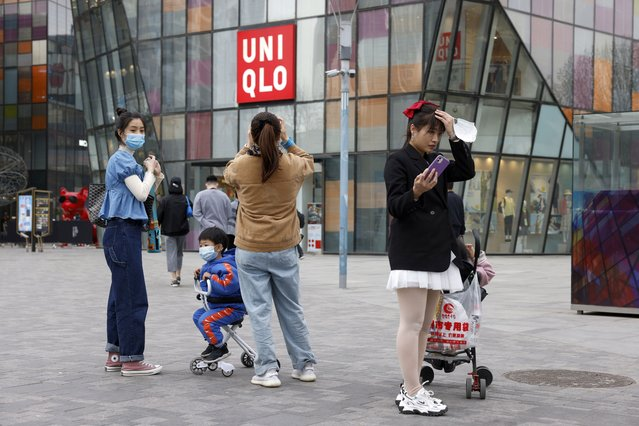 Visitors to a shopping mall wearing masks stand before a Uniqlo store in Beijing on Monday, March 29, 2021. (Photo by Ng Han Guan/AP Photo)