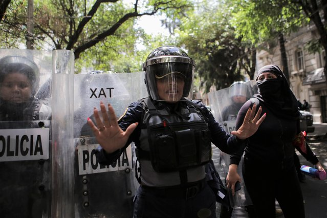 A police officer gestures during a protest in support of Victoria Salazar, a Salvadoran woman who died after a Mexican female police officer was seen in a video kneeling on her back, in Mexico City, Mexico on April 2, 2021. (Photo by Raquel Cunha/Reuters)