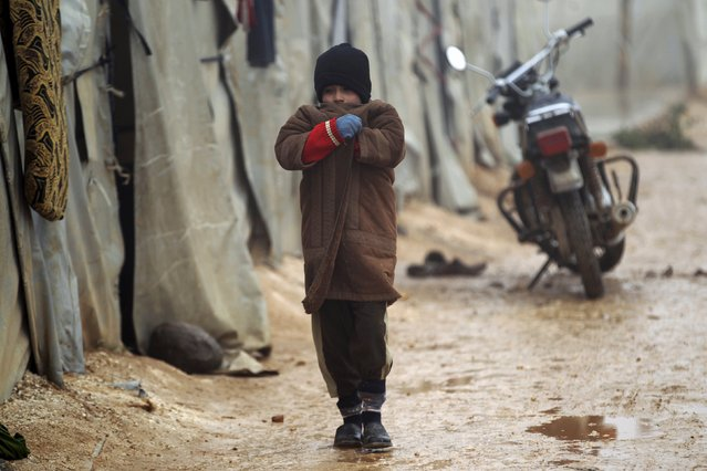A boy walks outside tents housing internally displaced people, during the cold weather in Jerjnaz camp, in Idlib province, Syria, January 5, 2016. (Photo by Khalil Ashawi/Reuters)