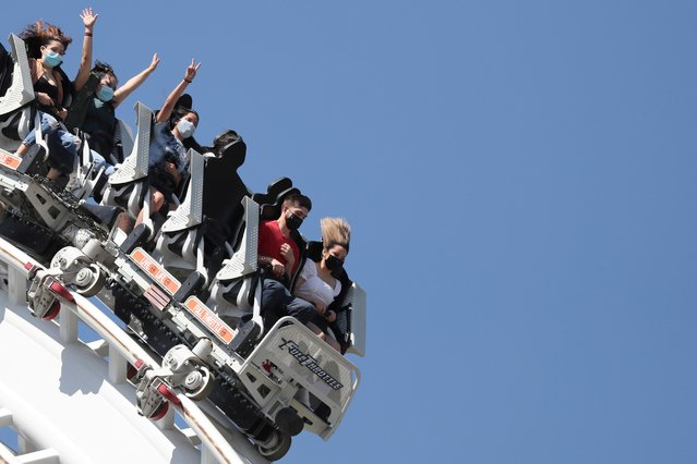 People ride a roller coaster at Six Flags Magic Mountain amusement park on the first day of opening, as the coronavirus disease (COVID-19) continues, in Valencia, California, U.S., April 1, 2021. (Photo by Lucy Nicholson/Reuters)