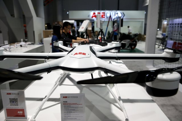 Workers set up a commercial drone display at the AEE Technology booth in the Las Vegas Convention Center during set-up for the 2016 CES trade show in Las Vegas, Nevada, January 5, 2016. In the foreground is a F600 all-weather, carbon fiber drone. The large size means the the drone can carry a larger payload and has better stability in wind, a representative said. (Photo by Steve Marcus/Reuters)