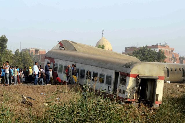 People gather at the site where a passenger train derailed injuring at least 100 people, near Banha, Qalyubia province, Egypt, Sunday, April 18, 2021. (Photo by Tarek Wagih/AP Photo)