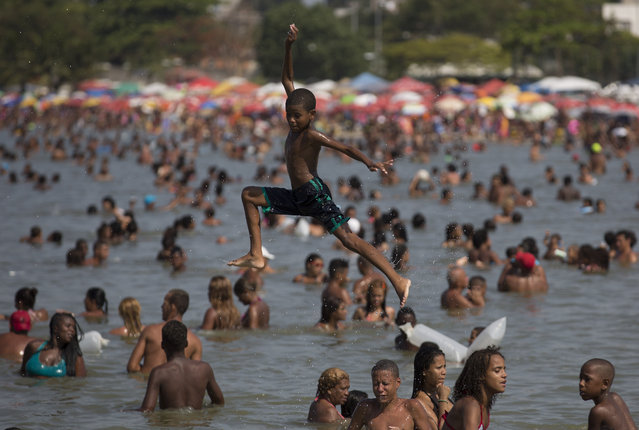 """In this January 20, 2015 photo, a kid plays at the artificial beach Piscinao de Ramos or the """"Big Pool of Ramos"""" in Rio de Janeiro, Brazil. (Photo by Leo Correa/AP Photo)"""