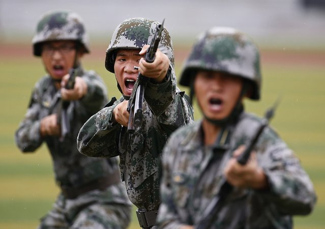 People's Liberation Army (PLA) soldiers shout as they hold guns and practise in a drill during a organized media tour at a PLA engineering school in Beijing in this July 22, 2014 file photo. (Photo by Petar Kujundzic/Reuters)