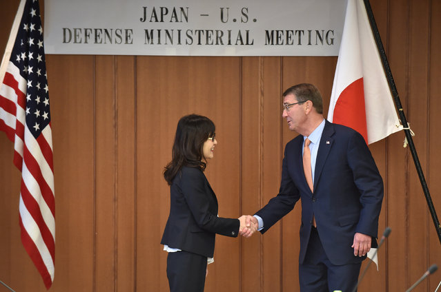 U.S. Defense Secretary Ash Carter and Japan's Defense Minister Tomomi Inada (L) shake hands before their meeting at the Defense Ministry in Tokyo, Japan, December 7, 2016. (Photo by Kazuhiro Nogi/Reuters)