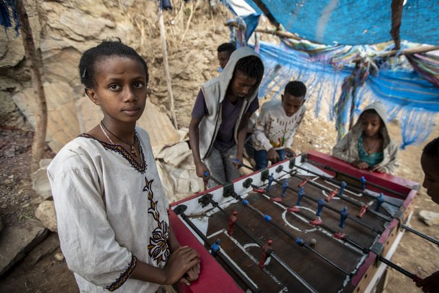 A girl watches while boys and young men play table football on the street, as Ethiopian Orthodox Christians celebrate Easter Sunday, in Gondar, in the Amhara region of Ethiopia Sunday, May 2, 2021. (Photo by Ben Curtis/AP Photo)