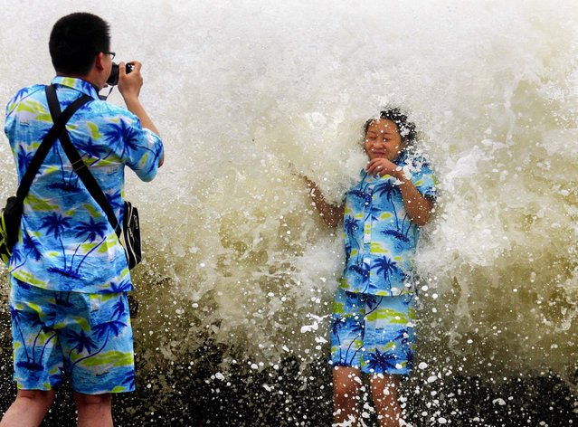 Tourists take pictures as a storm surge hits the coastline under the influence of Typoon Wutip in Sanya, Hainan province, on September 30, 2013. China's maritime authority on Monday issued a yellow wave warning as Typhoon Wutip, the 21st of the season, approaches. China has a four-tier color-coded weather warning system, with red representing the most severe weather, followed by orange, yellow and blue. (Photo by Reuters)
