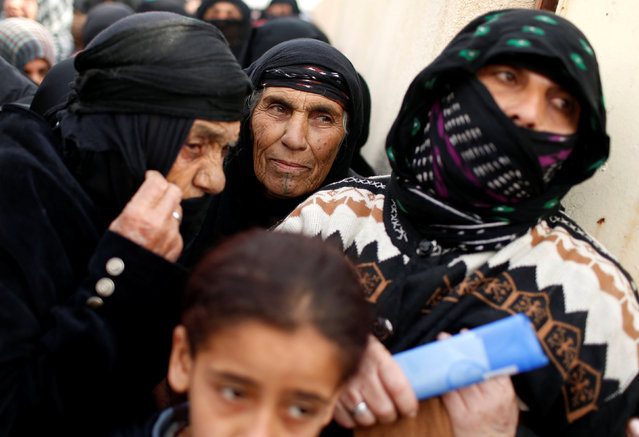 Iraqi women wait outside a distribution point run by United Nations agencies at Zahra district, east of Mosul, Iraq December 8, 2016. (Photo by Ahmed Jadallah/Reuters)