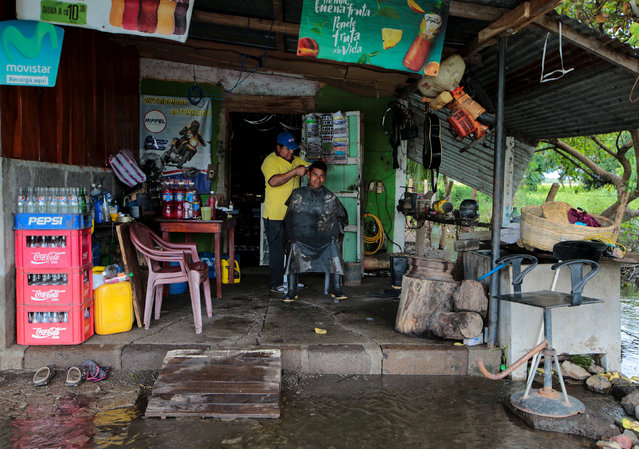 A barber cuts hair at his house, flooded by heavy rains in Malacatoya town, Nicaragua on October 9, 2018. (Photo by Oswaldo Rivas/Reuters)