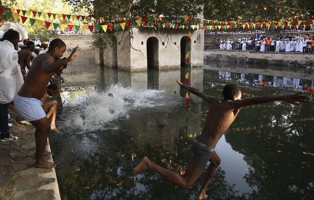 Faithful jump into the waters of Fasilides Bath as part of a ceremony in which the waters are blessed by the priest of Ethiopian Orthodox Tewahedo church during the second day of Timket in Gondar, Ethiopia, January 20, 2016. (Photo by Tiksa Negeri/Reuters)