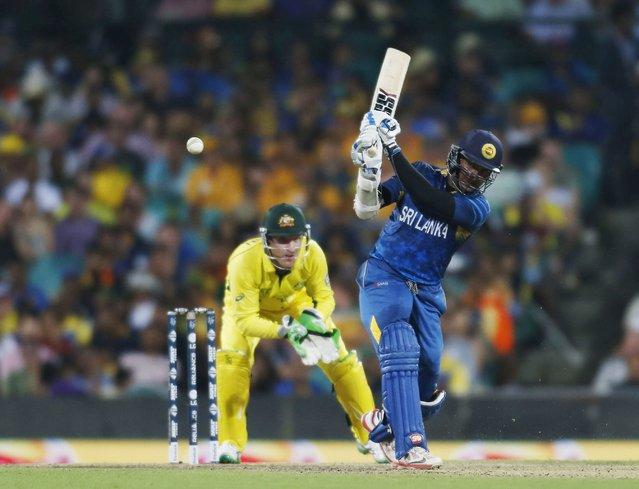 Australia's Brad Haddin (L) looks on as Sri Lanka's Kumar Sangakkara hits a shot during their Cricket World Cup match in Sydney, March 8, 2015.    REUTERS/Jason Reed (AUSTRALIA - Tags: SPORT CRICKET)
