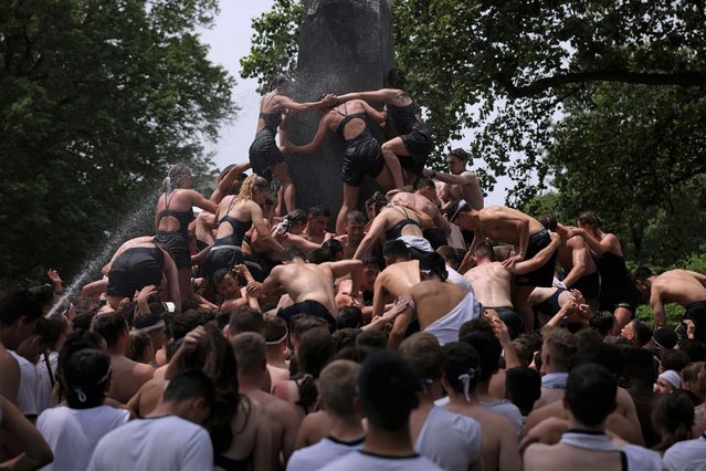 """Members of the 2024 midshipmen's class (freshman) from the U.S. Naval Academy work to scale the Herndon Monument and place an upperclassman's hat on the 21-foot obelisk on on May 22, 2021 in Annapolis, Maryland. The """"plebes"""" worked for three hours and forty one minutes to scale the 21-foot monument and replace a """"dixie cup"""" with the upperclassmen hat, signifying the end of their """"plebe"""" year. (Photo by Anna Moneymaker/Getty Images)"""