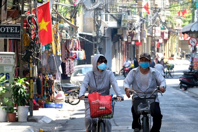 People ride bicycles in Hanoi, Vietnam, 30 May 2021. Vietnam has recently detected a new coronavirus variant which combines the Indian and UK COVID-19 variants, according to Vietnamese Health Minister Nguyen Thanh Long. (Photo by Luong Thai Linh/EPA/EFE)