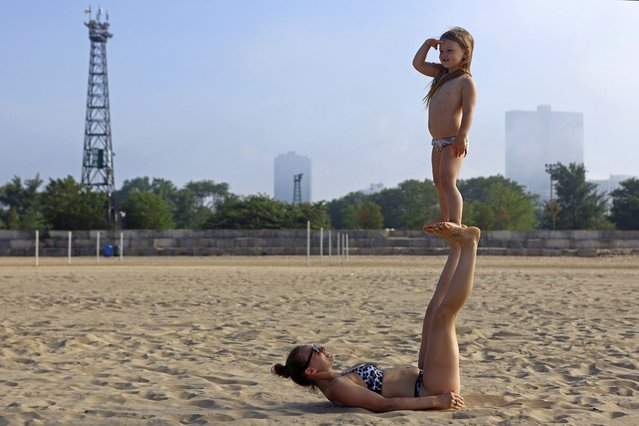 Uma Johansson, 5, balances on the feet of her mother Alina Anaite as they enjoy their time in Chicago's Montrose Beach, Wednesday, June 9, 2021. The beaches in Chicago have reopened since closing over a year ago because of the coronavirus pandemic. (Photo by Shafkat Anowar/AP Photo)