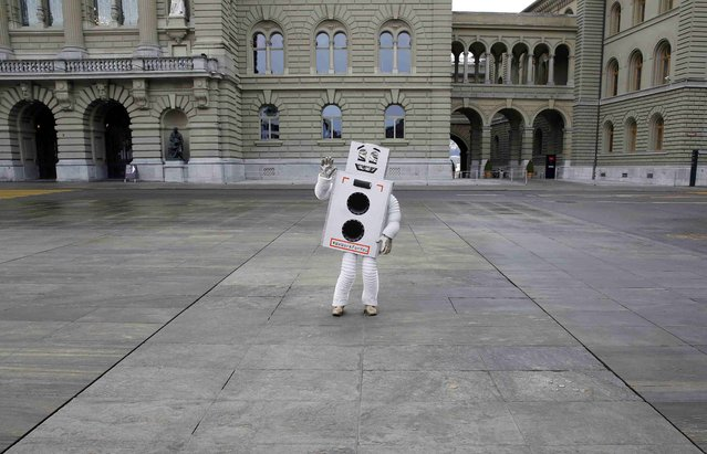 A participant of the initiative for an Unconditional Basic Income, dressed as a robot, dances on the Federal Square in Bern, Switzerland January 27, 2016. Switzerland will vote on the initiative for an Unconditional Basic Income this year. (Photo by Ruben Sprich/Reuters)