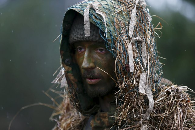 A man takes part in a territorial defence training organised by paramilitary group SJS Strzelec (Shooters Association) in the forest near Minsk Mazowiecki, eastern Poland March 14, 2014. (Photo by Kacper Pempel/Reuters)