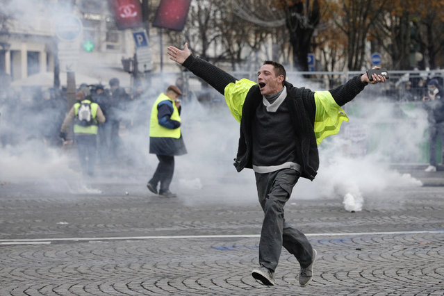 A demonstrator braves the tear gas during clashes on the famed Champs-Elysees avenue in Paris, as he protests with others against the rising of the fuel taxes, France, Saturday, November 24, 2018. France is deploying thousands of police to try to contain nationwide protests and road blockades by drivers angry over rising fuel taxes and Emmanuel Macron's presidency. (Photo by Kamil Zihnioglu/AP Photo)