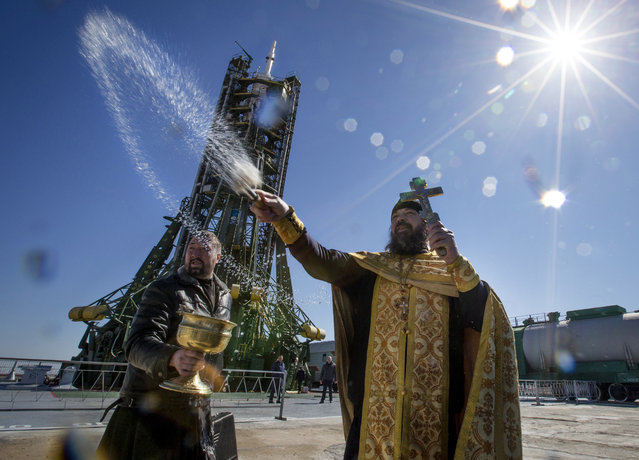 An Orthodox priest conducts a blessing service in front of the Soyuz TMA-16M spacecraft at the Russian leased Baikonur cosmodrome, Kazakhstan, Thursday, March 26, 2015. The new Soyuz mission is scheduled for Saturday, March 28. (Photo by Dmitry Lovetsky/AP Photo)