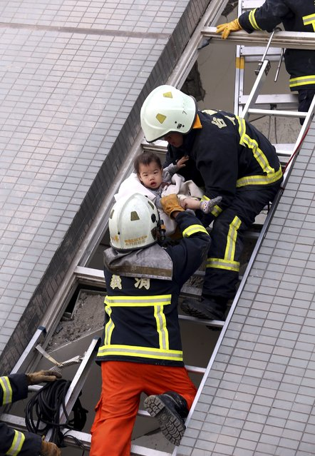 Firemen rescue a baby from a collapsed building in Tainan City, Taiwan, 06 February 2016, following a 6.4 magnitude earthquake that struck the area. At least three people, including an infant, were killed and 45 injured when several buildings, including a 17-storey building, collapsed after a 6.4-magnitude earthquake struck southern Taiwan early 06 February, authorities said. (Photo by Johnson Liu/EPA)