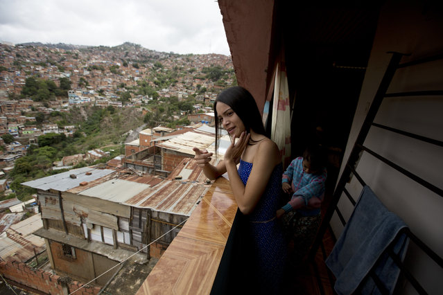 """In this July 1, 2018 photo, Johandrys Colls, left, speaks with her sister Camila on the balcony of their home, in a slum on the outskirts of Caracas, Venezuela. Colls still remembers watching the Miss Venezuela pageant with her family at 6-years-old and then stealing her mom's high heels to imitate the beauty queens on screen. """"It's inspiring"""", she said, her lips curling into a smile at the memory. """"It's something beautiful to see them compete and share their talent with the world"""". (Photo by Fernando Llano/AP Photo)"""