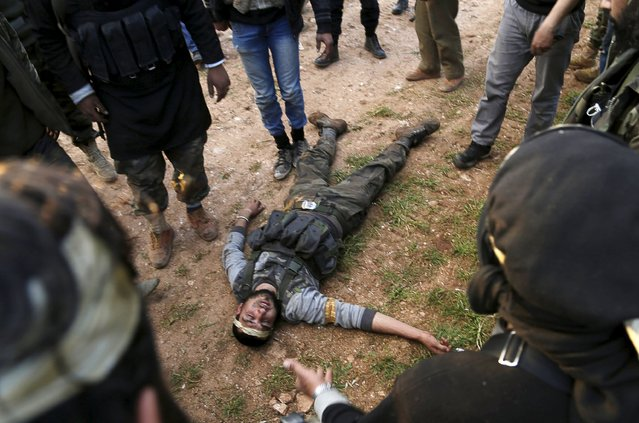 An injured rebel fighter from the Ahrar al-Sham Islamic Movement lies on the ground during what the rebel fighters said was an offensive to take the northwestern city of Idlib March 24, 2015. (Photo by Khalil Ashawi/Reuters)