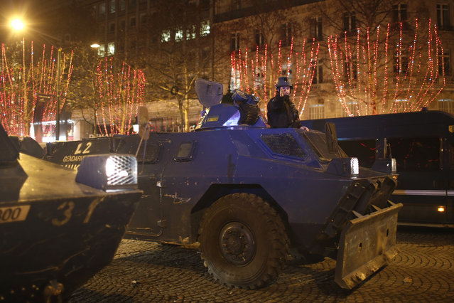 An armored military vehicle drives down the Champs-Elysees avenue after clashes Saturday, December 8, 2018 in Paris. (Photo by Rafael Yaghobzadeh/AP Photo)
