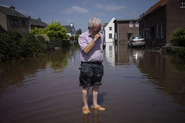 Wiel de Bie, 75,  stands outside his flooded home in the town of Brommelen, Netherlands,  Saturday, July 17, 2021. In the southern Dutch province of Limburg, which also has been hit hard by flooding, troops piled sandbags to strengthen a 1.1-kilometer (0.7 mile) stretch of dike along the Maas River, and police helped evacuate low-lying neighborhoods. (Photo by Bram Janssen/AP Photo)