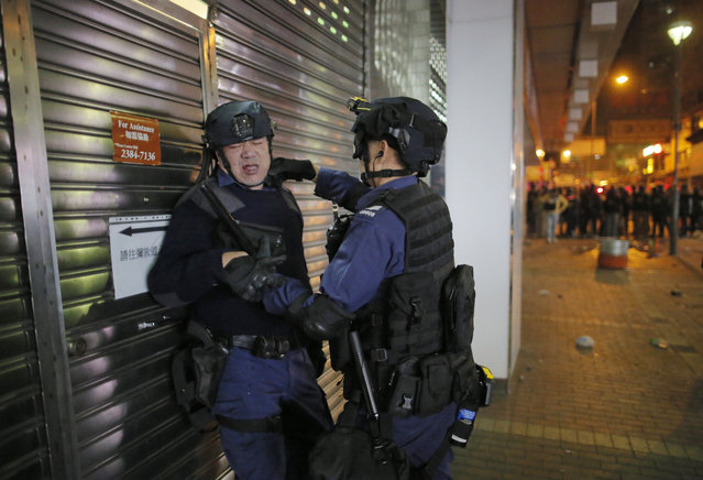 An injured rioter police is attended by a colleague as rioters set fires and throw bricks at them in Mong Kok district of Hong Kong, Tuesday, February 9, 2016. (Photo by Vincent Yu/AP Photo)