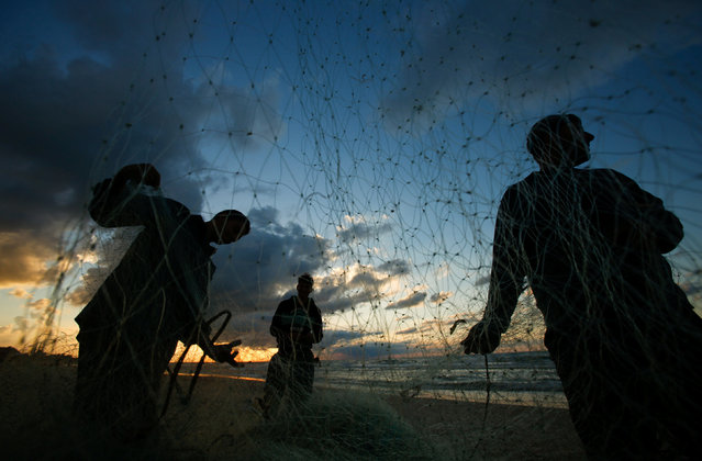 Palestinian fishermen fix their net at the beach of northern of Gaza Strip, December 17, 2016. (Photo by Suhaib Salem/Reuters)
