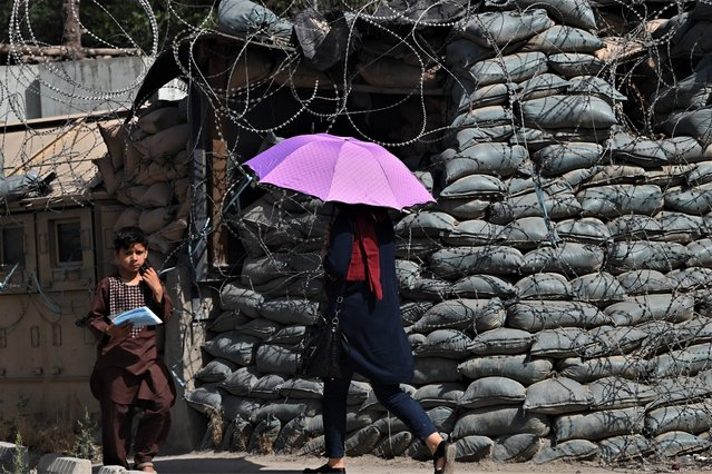 People walk past a security post covered in barbed wire in Kabul on June 10, 2021. (Photo by Adek Berry/AFP Photo)