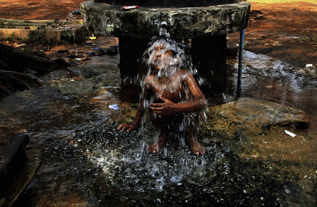 An Indian boy takes bath under a roadside public water supply tap on a hot afternoon in the eastern Indian city of Bhubaneswar, India, Friday, March 27, 2015. (Photo by Biswaranjan Rout/AP Photo)