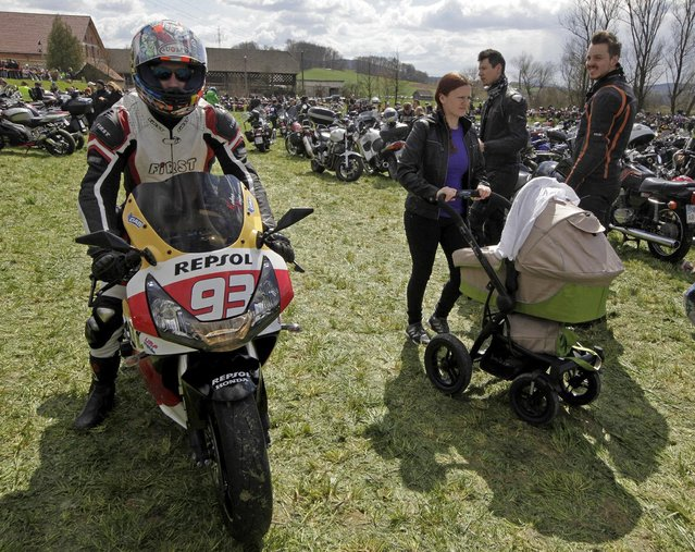 A motorist rides a motorcycle next to a woman with a pram during the first gathering of motorists at the beginning of the spring season in Mirna Pec April 6, 2015. (Photo by Srdjan Zivulovic/Reuters)
