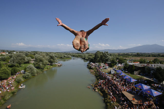 Spectators watch from the river banks as a diver launches from the Ura e Shejnt bridge during the 68th traditional annual high diving competition, near the town of Gjakova, Kosovo on Sunday, July 22, 2018. (Photo by Visar Kryeziu/AP Photo)