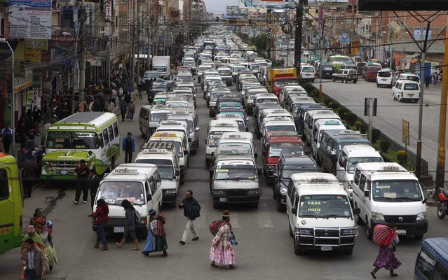 In this December 9, 2013 photo, traffic at a standstill as pedestrians cross a street in El Alto, Bolivia. The Bolivian highlands' city has hired Aymara women dressed in traditional multi-layered Andean skirts and brightly embroidered vests to work as traffic cops and bring order to its road chaos. (Photo by Juan Karita/AP Photo)