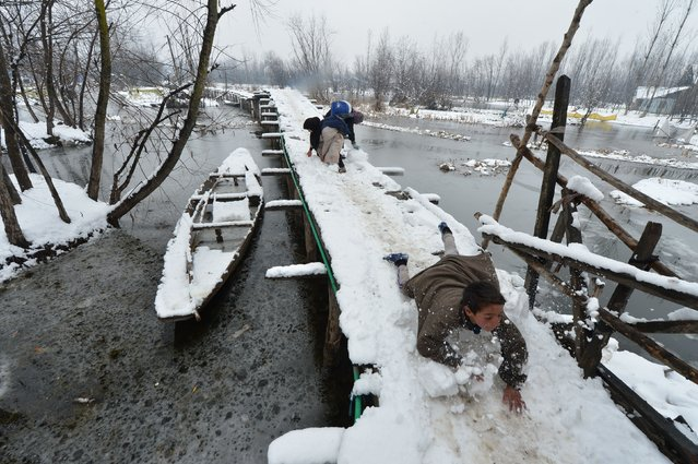 Kashmiri children play with snow on a wooden foot bridge in the interiors of Dal Lake in Srinagar on January 16, 2017. A cold wave has further tightened its grip in Jammu and Kashmir, with most places in the state recording sub-zero temperatures. (Photo by Tauseef Mustafa/AFP Photo)