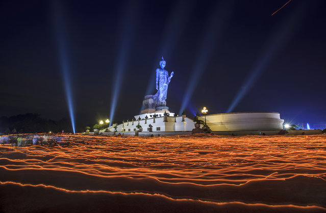 People walk around the Buddha Statue holding candles for prayers during Makha Bucha Day at Buddhist Park on February 25, 2013 in Nakhon Pathom, Thailand.  (Photo by Athit Perawongmetha/Getty Images)