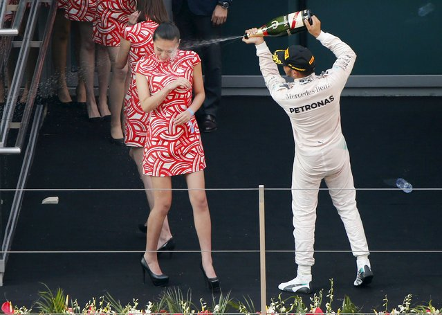 Mercedes Formula One driver Lewis Hamilton of Britain sprays champagne at a grid girl as he celebrates his victory on the podium after the Chinese F1 Grand Prix at the Shanghai International Circuit, April 12, 2015. (Photo by Carlos Barria/Reuters)