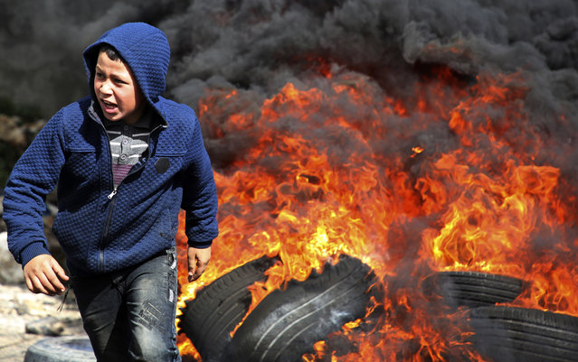A Palestinian protester runs away from flaming tyres during a weekly demonstration against the expropriation of Palestinian land by Israel, in the village of Kfar Qaddum, near Nablus in the occupied West Bank, on February 8, 2019. (Photo by Jaafar Ashtiyeh/AFP Photo)