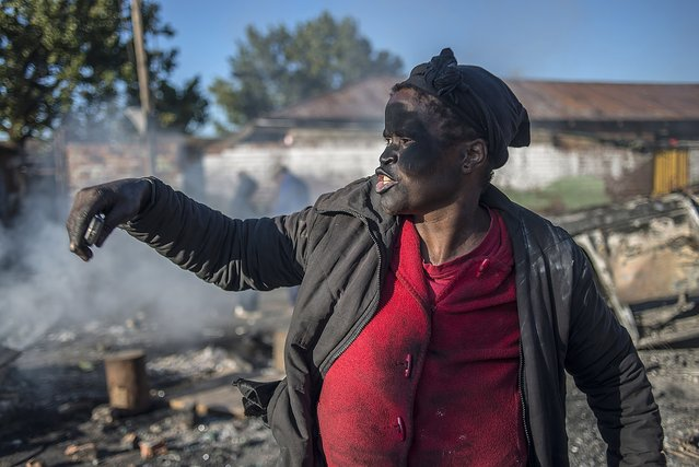 A women covered in soot gestures and shouts towards foreign nationals outside the Jeppies Hostles, in the Jeppestown area of Johannesburg, on April 17, 2015 after residence from the Jeppie Hostles, purportedly torched a passing vehicle in the early hours.  Twelve people were arrested overnight as anti-foreigner attacks in South Africa spread to parts of downtown Johannesburg, police said. (Photo by Mujahid Safodien/AFP Photo)