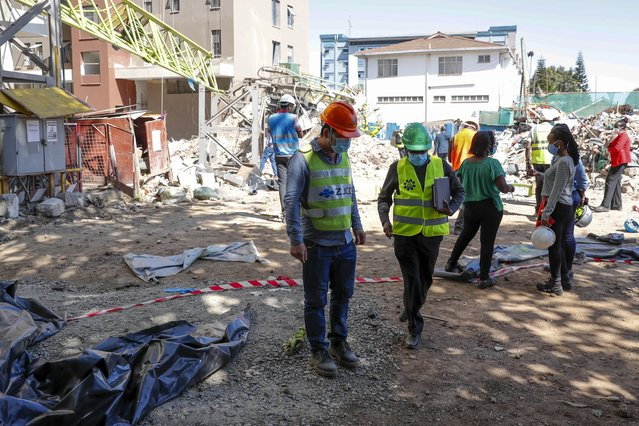 Construction workers observe the wreckage after a crane collapsed at a construction project to build a 14-storey student hostel in Nairobi, Kenya, Thursday, August 26, 2021. Police in Kenya's capital say nine people are dead, including two Chinese engineers, after the crane collapsed at the site being supervised by a Chinese construction firm. (Photo by Brian Inganga/AP Photo)